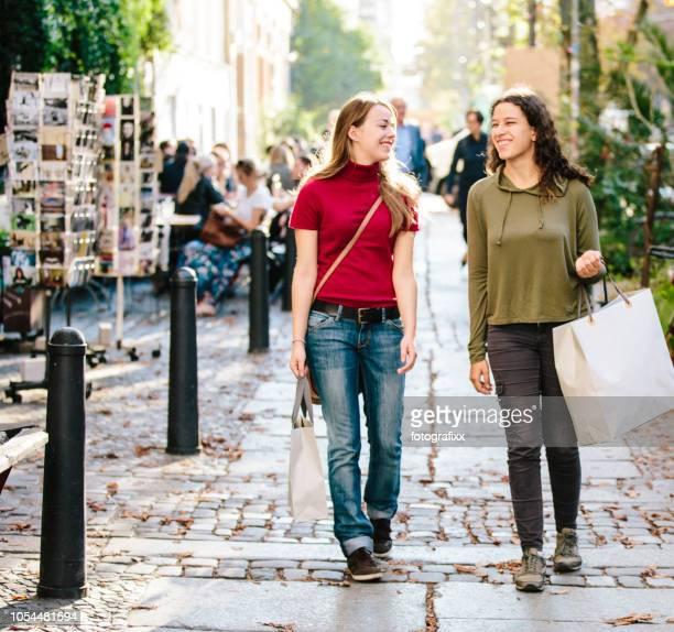 Einkaufen: zwei junge Frauen mit Einkaufstaschen zu Fuß die Straße