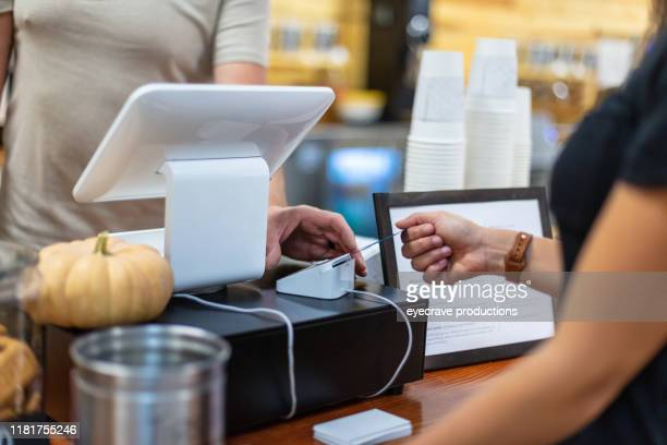 shopping using credit card women young millennial hand inserting card into chip reader in western colorado indoors at a coffee shop - credit score stock pictures, royalty-free photos & images