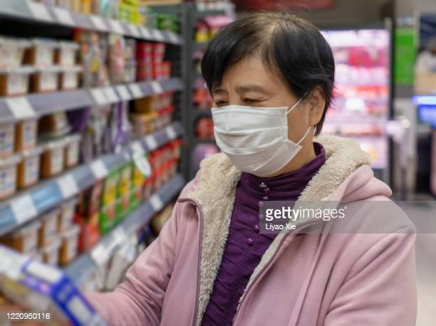 shopping with mask - liyao xie stock pictures, royalty-free photos & images