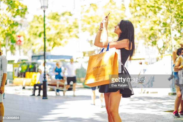 shopping woman, barcelona - spain - louis vuitton designer label stock photos and pictures