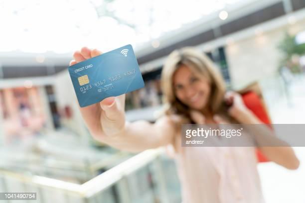 mulher segurando um cartão de crédito no shopping de compras - foco no primeiro plano - fotografias e filmes do acervo
