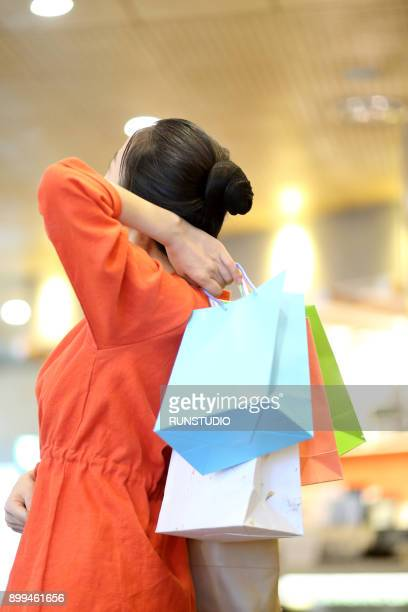 shopping woman holding shopping bags - rear view