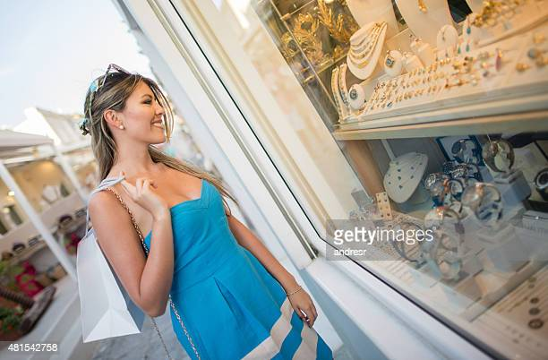 Shopping woman looking at the window of a jewelry store