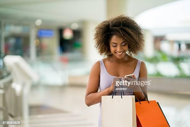 shopping mulher mensagens de texto em seu telefone - comércio consumismo - fotografias e filmes do acervo