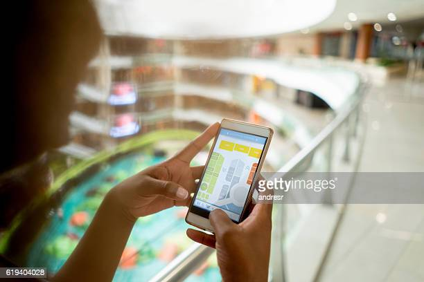 shopping woman using her cell phone at the mall - karte navigationsinstrument stock-fotos und bilder