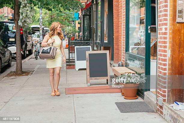 nyc shopping woman walking looks at retail window displays - soho new york stock pictures, royalty-free photos & images