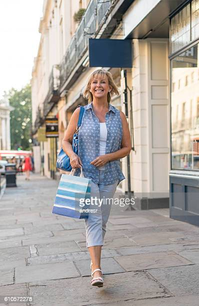 shopping woman walking on the street - only mature women stock pictures, royalty-free photos & images