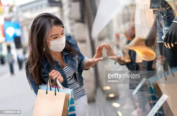 shopping woman wearing a facemask during the pandemic and looking at a window - buying stock pictures, royalty-free photos & images