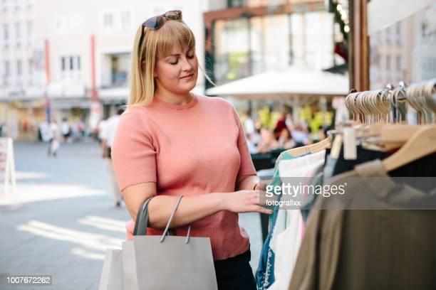 einkaufen: junge frau sucht kleider bei kleiderstange - blond mollig frau stock-fotos und bilder