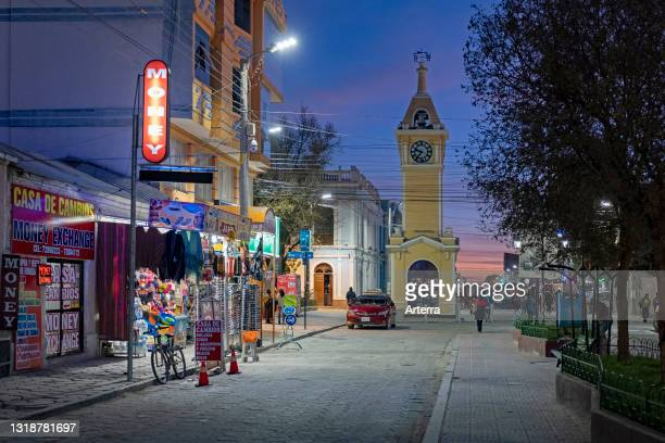 Shops in the main street and yellow clock tower in the city Uyuni after sunset, Antonio Quijarro Province, Potosí Department, Bolivia.