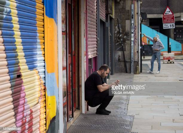 Shops-owners wait outside their shops in a quiet street in London on November 10, 2020. - Britain's unemployment rate has jumped to 4.8 percent as...
