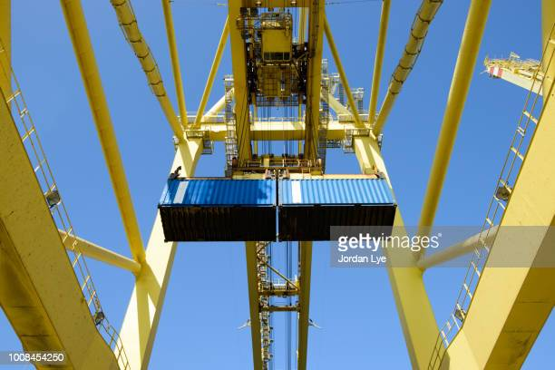 shore crane loading containers in freight ship - 積荷を降ろす ストックフォトと画像