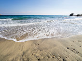 Shore of the beach with water waves color turquoise that they break on the brown sand. Cabo de Gata - Nijar Natural Park, Cala del Plomo, Beach, Biosphere Reserve, Almeria,  Andalusia, Spain