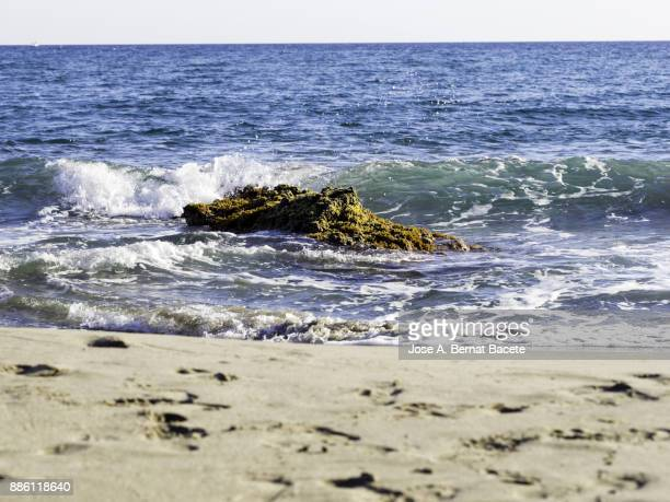 Shore of the beach with water waves color turquoise that they break in the rocks. Cabo de Gata - Nijar Natural Park, Cala del Plomo, Beach of Genoveses, Biosphere Reserve, Almeria,  Andalusia, Spain