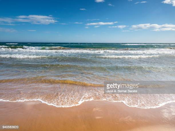 shore of the beach with water waves color turquoise that they break on the brown sand. - midday stock pictures, royalty-free photos & images