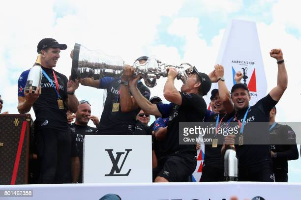 Shore Team Coordination and Boat building member Sean Regan of Emirates Team New Zealand drinnks champagne from the trophy as Peter Burling looks on...