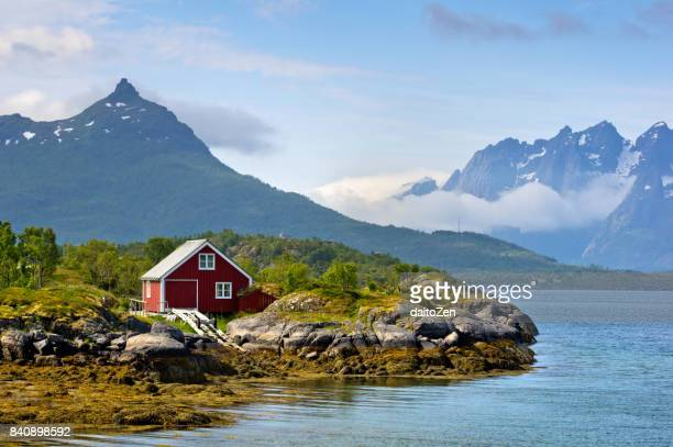 Shoreline of Raftsund strait with red-painted house and Trolltinden mountain range, Lofoten Islands, Nordland, Norway