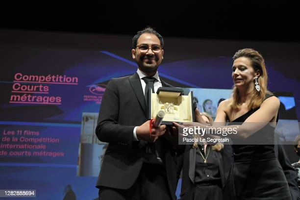 Short film Palme d'Or winner Sameh Alaa poses on stage with jury member Celine Sallette during the Best Short Film Palme D'Or Award Ceremony of the...