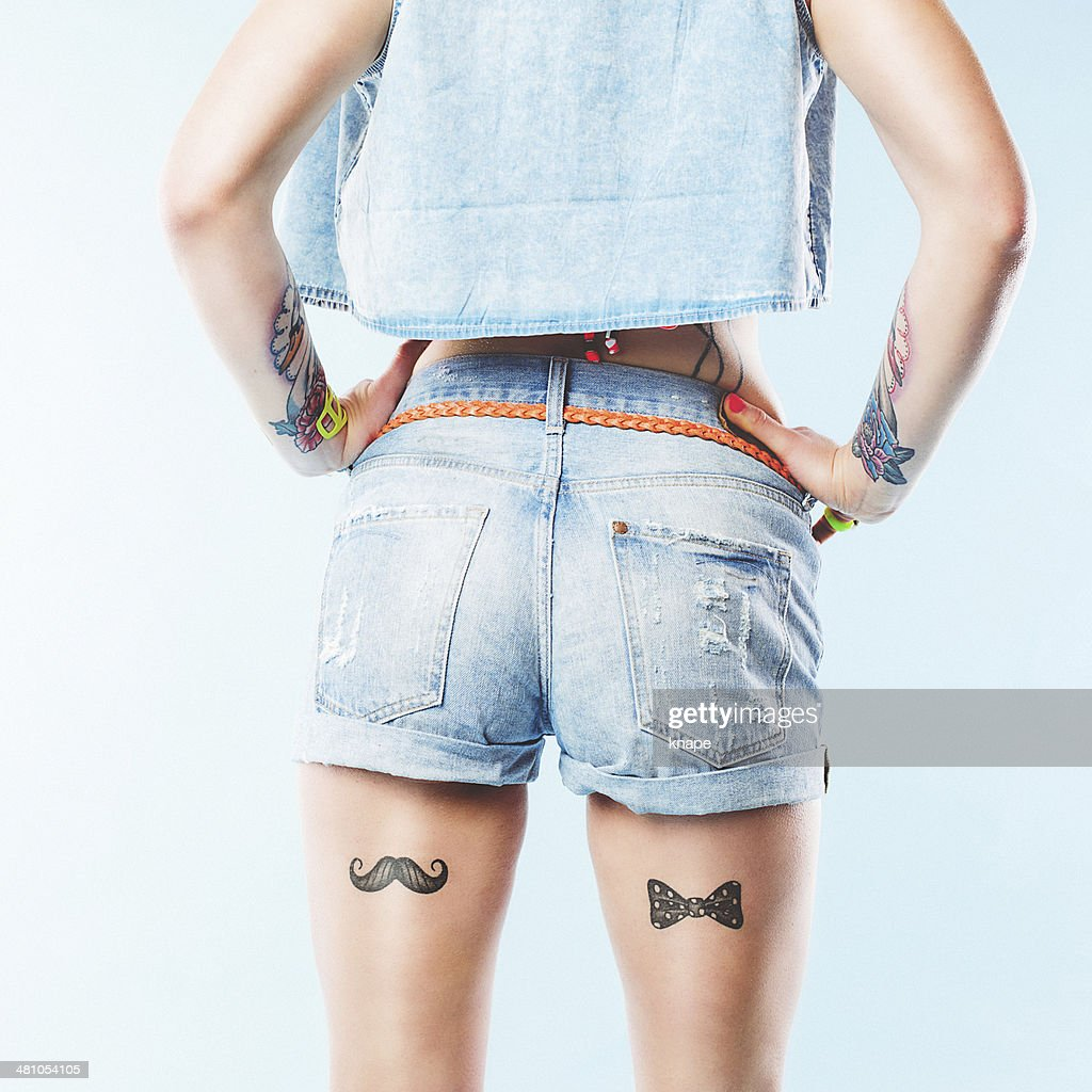 Short jeans shorts and leg tattoos : Stock Photo