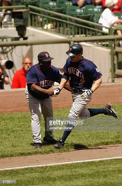 Short stop Denny Hocking of the Minnesota Twins is congratulated by third base coach Al Newman as he heads home during the interleague game against...