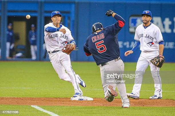 Short Stop Ryan Goins of the Toronto Blue Jays turns the double play to end the top of the 4th inning as Allen Craig of the Boston tries to break up...