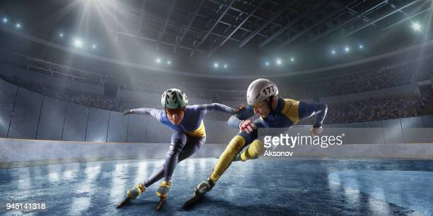 short track athletes slide in professional ice arena. fall of a skater - ski racing stock pictures, royalty-free photos & images
