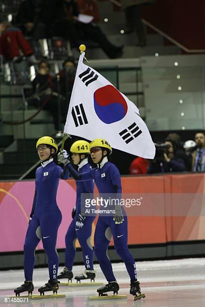 Short Track Skating: 2006 Winter Olympics, South Korea Sun-Yu Jin , South Korea Eun-Kyung Choi , and South Korea Chun-Sa Byun victorious with flag...