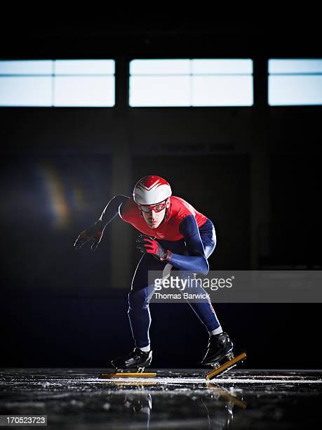 Short track speed skater prepared to start sprint