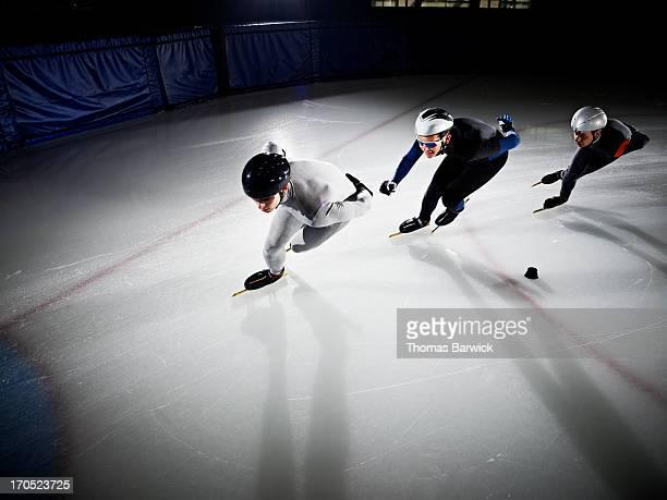 short track speed skaters in turn during race - koordination stock-fotos und bilder