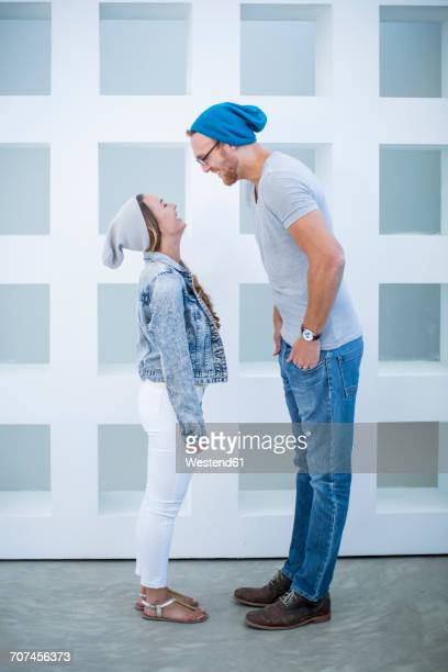 Short woman and tall man laughing at each other