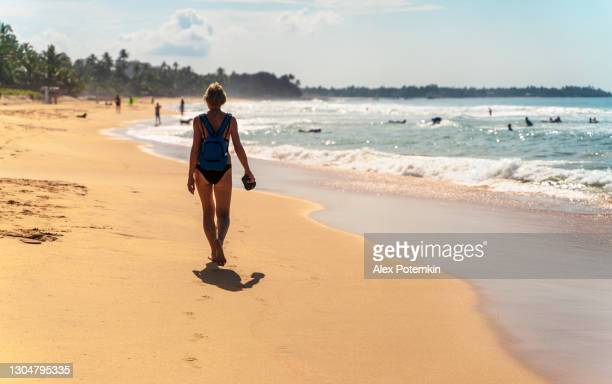 short-haired european woman, a tourist, is walking on a tropical beach, with surfers practicing in the backdrop - sea swimming stock pictures, royalty-free photos & images