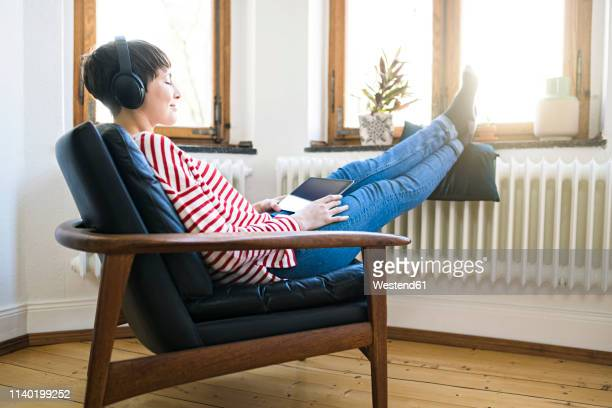short-haired woman with headphones relaxing in lounge chair in stylish apartment - convenience stock photos and pictures