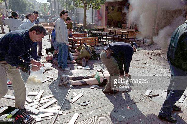 Shortly after a Palestinian suicide bomber blew himself up January 25 2002 in Tel Aviv Israeli medics treat victims of the blast as black smoke...