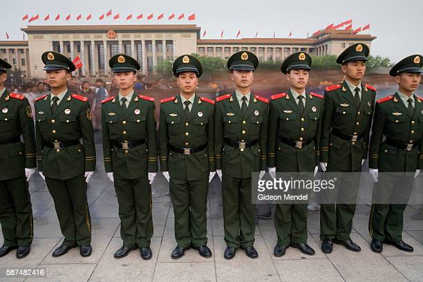 Shortly after sunrise on Mayday a a row of Chinese soldiers stand strictly to attention in Tiananmen Square In the background is the Great Hall of...