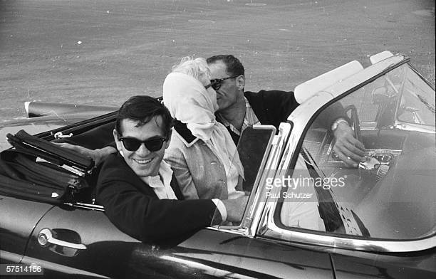 Shortly after their marriage American actress Marilyn Monroe and American playwright Arthur Miller kiss in a convertible while Monroe's close friend...