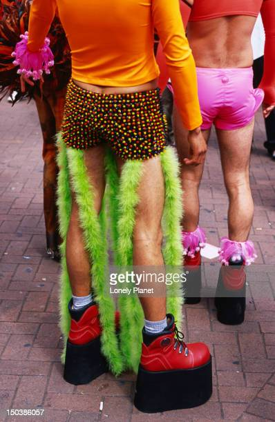 Shorts, legs and shoes of colourfully dressed participants during parade at London Pride.