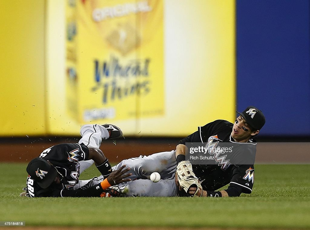 Shortstop Adeiny Hechavarria #3 and left fielder Christian Yelich #21 of the Miami Marlins both dive but can't make a catch on a ball hit by Daniel Murphy #28 of the New York Mets for an RBI double during the ninth inning on May 29, 2015 at Citi Field in the Flushing neighborhood of the Queens borough of New York City. The Marlins defeated the Mets 4-3.