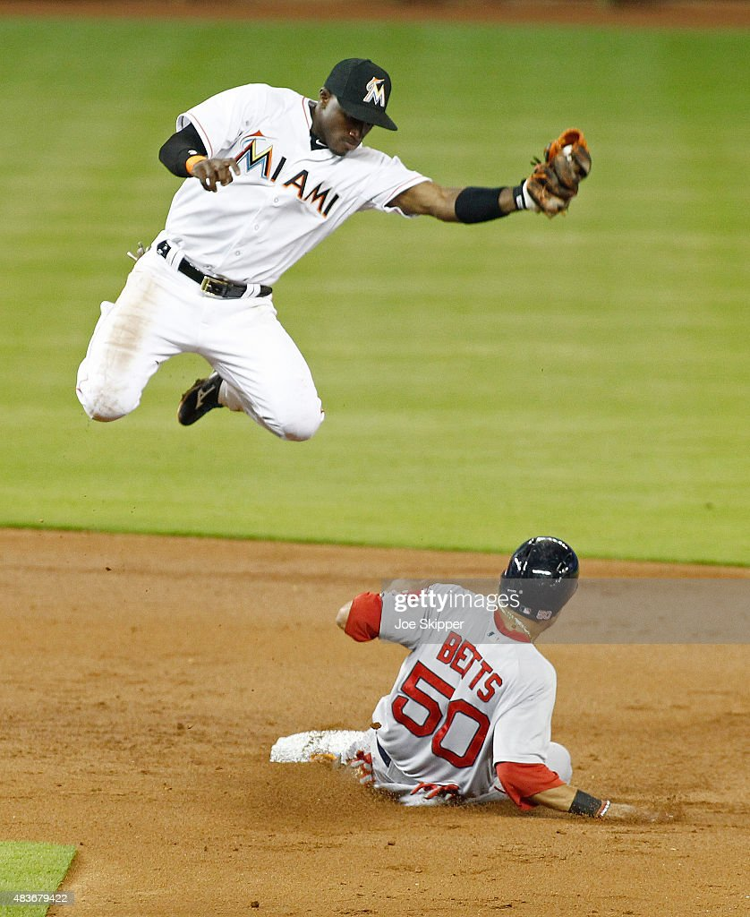 Shortstop Adeiny Hechavarria #3 of the Miami Marlins leaps for a high throw but can't catch baserunner Mookie Betts #50 of the Boston Red Sox who stole second base in the third inning at Marlins Park on August 11, 2015 in Miami, Florida.