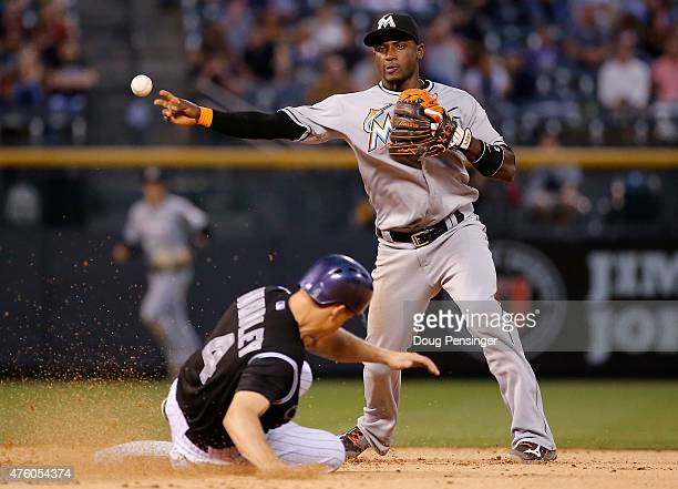 Shortstop Adeiny Hechavarria of the Miami Marlins turns a double play on Nick Hundley of the Colorado Rockies on a ground ball by Brandon Barnes of...