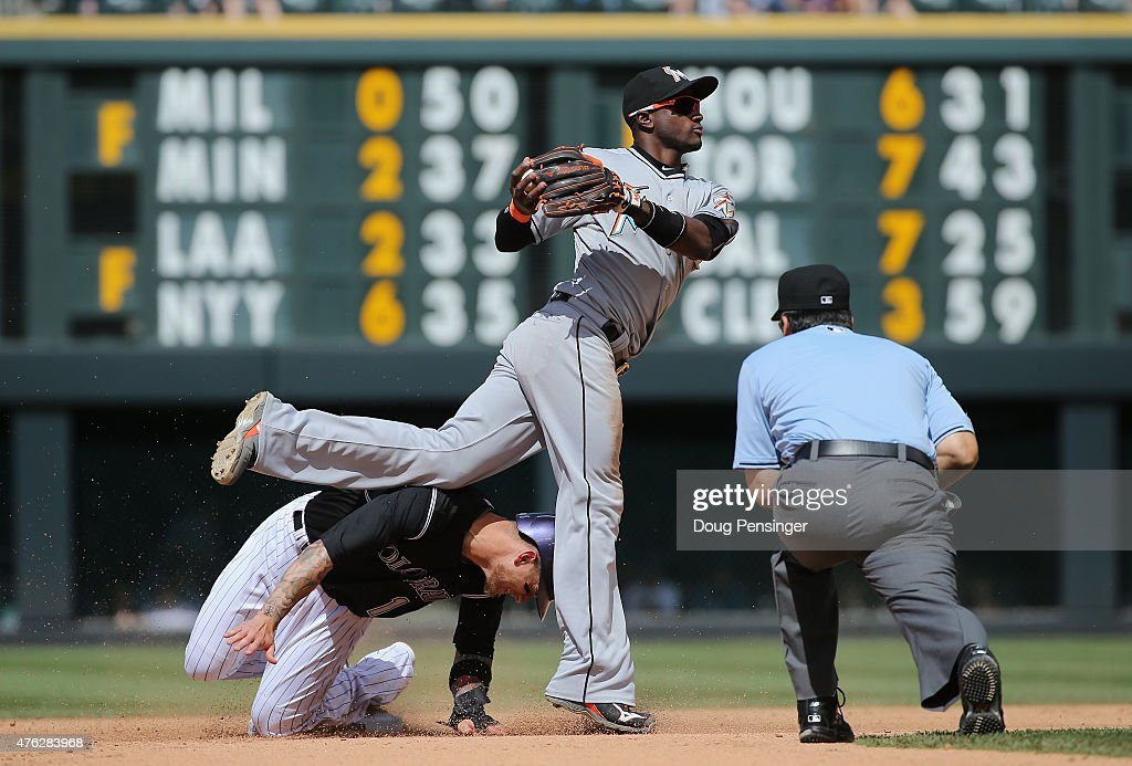 Shortstop Adeiny Hechavarria #3 of the Miami Marlins turns a double play on Brandon Barnes #1 of the Colorado Rockies on a bunt attempt by Kyle Kendrick #38 of the Colorado Rockies as umpire Phil Cuzzi oversees the action in the fifth inning at Coors Field on June 7, 2015 in Denver, Colorado.