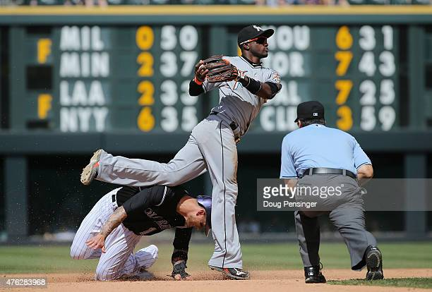 Shortstop Adeiny Hechavarria of the Miami Marlins turns a double play on Brandon Barnes of the Colorado Rockies on a bunt attempt by Kyle Kendrick of...