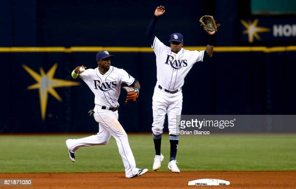 Shortstop Adeiny Hechavarria of the Tampa Bay Rays fields the ground out by Ruben Tejada of the Baltimore Orioles in front of second baseman Tim...