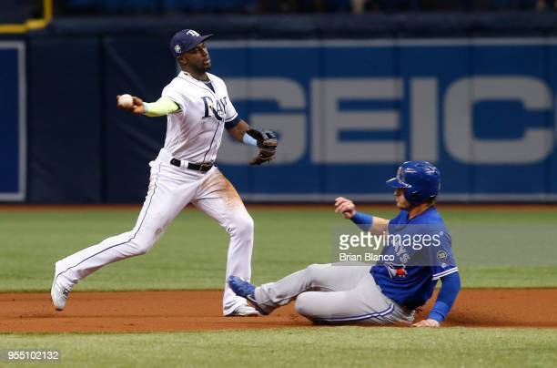 Shortstop Adeiny Hechavarria of the Tampa Bay Rays gets the out at second base on Josh Donaldson of the Toronto Blue Jays then turns the double play...