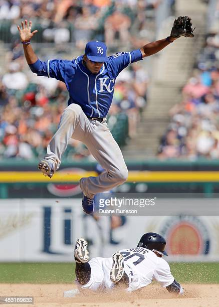 Shortstop Alcides Escobar of the Kansas City Royals jumps out of the way of Rajai Davis of the Detroit Tigers stealing second base when the pickoff...