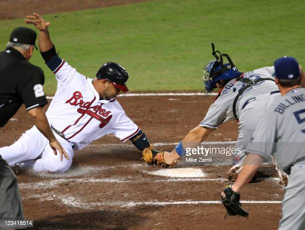 Shortstop Alex Gonzalez of the Atlanta Braves is tagged out at the plate by catcher Rod Barajas of the Los Angeles Dodgers while home plate umpire...