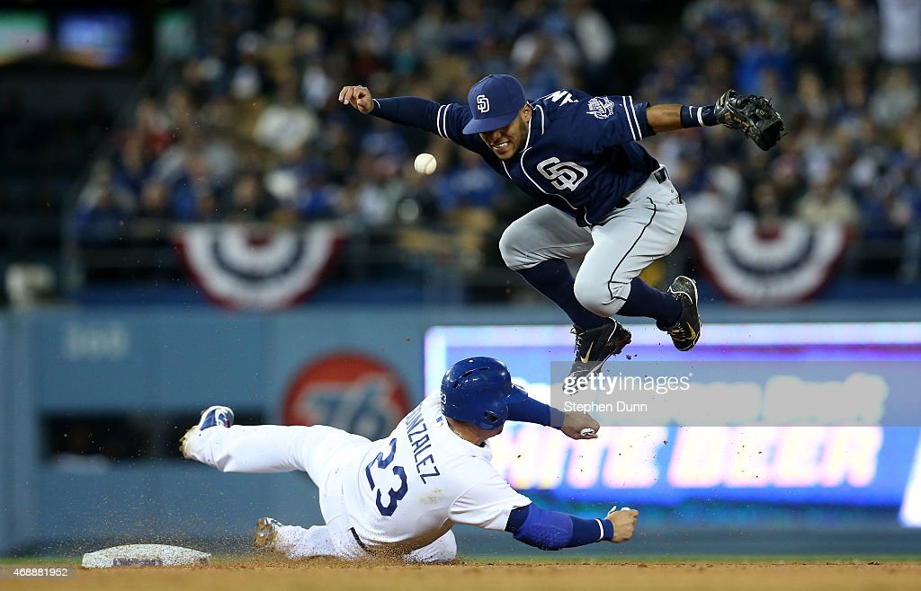 Shortstop Alexi Amarista #5 of the San Diego Padres loses the ball as he attempts to throw to complete a double play after forcing out Adrian Gonzalez #23 of the Los Angeles Dodgers in the fourth inning at Dodger Stadium on April 7, 2015 in Los Angeles, California. The Padres won 7-3.