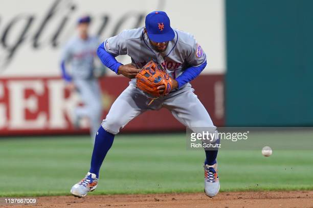 Shortstop Amed Rosario of the New York Mets makes an error his second of the inning on a ball off the bat of Aaron Altherr of the Philadelphia...