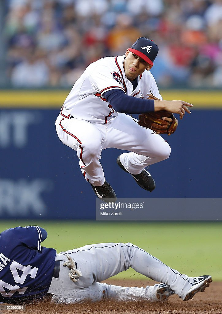 Shortstop Andrelton Simmons #19 of the Atlanta Braves turns a double play in the second inning while catcher Rene Rivera #44 of the San Diego Padres slides under him during the game at Turner Field on July 25, 2014 in Atlanta, Georgia.
