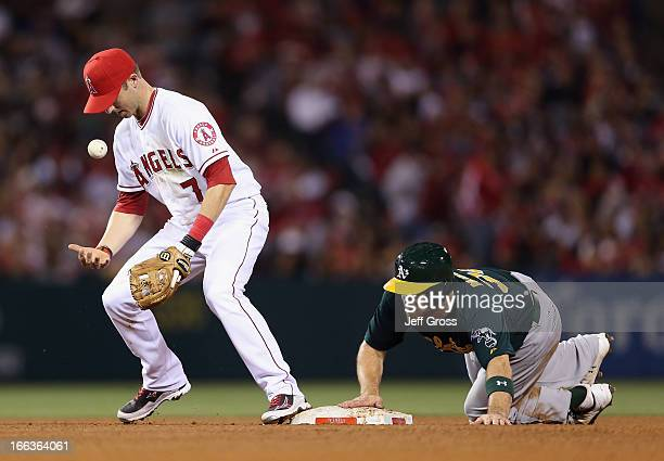 Shortstop Andrew Romine of the Los Angeles Angels of Anaheim bobbles the ball as Derek Norris of the Oakland Athletics steals second base in the...