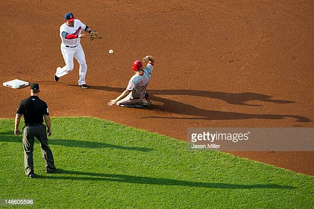 Shortstop Asdrubal Cabrera of the Cleveland Indians throws past Ryan Hanigan of the Cincinnati Reds for a double play during the first inning as...